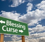 Blessing, Curse Green Road Sign Over Dramatic Blue Sky and Clouds.