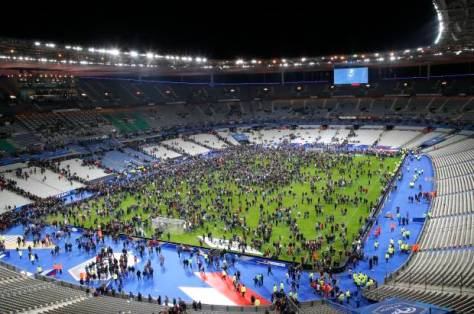 Spectators invade the pitch of the Stade de France stadium after the international friendly soccer France against Germany, Friday, Nov. 13, 2015 in Saint Denis, outside Paris. At least 35 people were killed in shootings and explosions around Paris, many of them in a popular theater where patrons were taken hostage, police and medical officials said Friday. Two explosions were heard outside the Stade de France stadium. (AP Photo/Michel Euler)