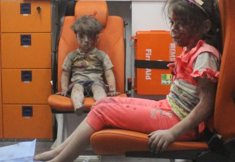 Five-year-old Omran Daqneesh, with bloodied face, sits with his sister inside an ambulance after they were rescued following an airstrike in the rebel-held al-Qaterji neighbourhood of Aleppo, Syria August 17, 2016. Picture taken August 17, 2016. REUTERS/Mahmoud Rslan